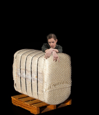 A beautiful young teenage woman leaning on a bale of raw cotton on a pallet photo