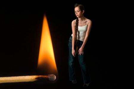 firestarter: Woman standing next to a burning match