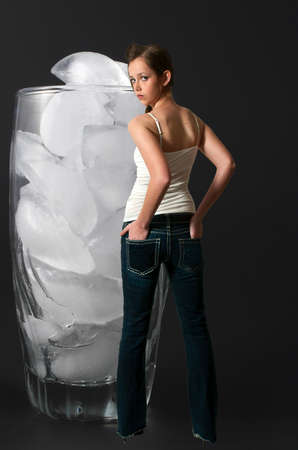 Beautiful young woman standing next to ice cubes in a clear water glass photo