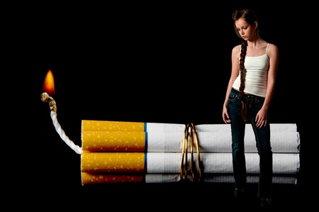 Beautiful teenage woman standing beside several cigarettes bound together like sticks of dynamite photo