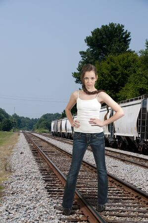 Young Beautiful Woman teenager girl posing on some train railroad tracks photo