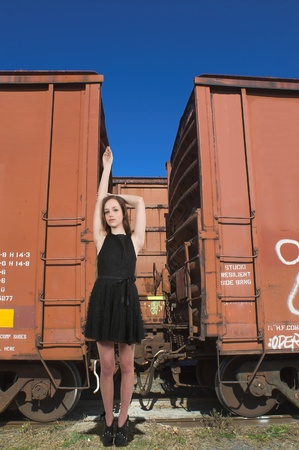 Beautiful teenage woman standing next to railway boxcars in a railroad yard