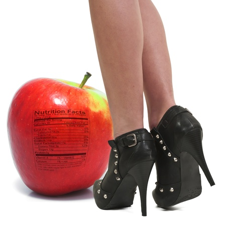 Beautiful womwns legs standing next to a whole red delicious apple with a nutrition label photo