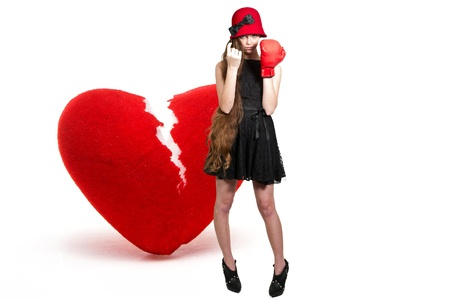 heartbreaker: A beautiful woman in wearing a boxing glove in front of a broken heart - heartbreaker Stock Photo