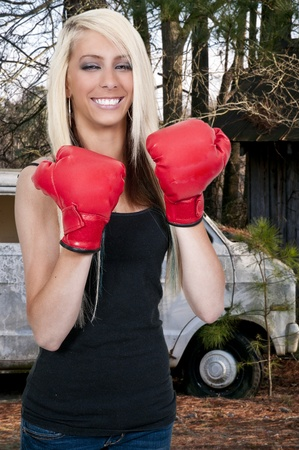 A beautiful young woman wearing a pair of boxing gloves photo