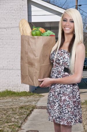Beautiful young woman with a brown paper shopping bag