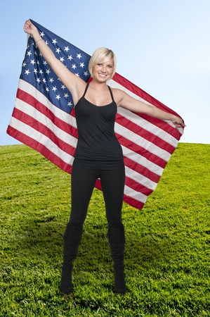 A beautiful young woman holding an American flag. Stock Photo - 12551657