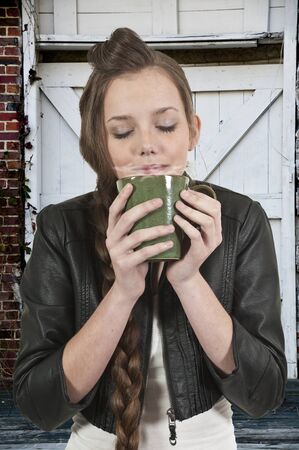 A beautiful young woman drinking and smelling coffee  Stock Photo