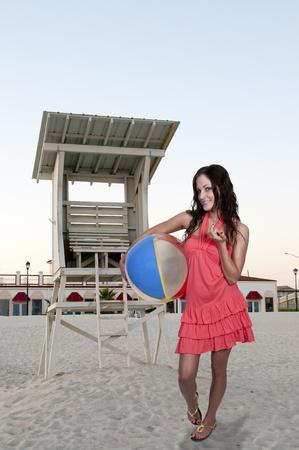 beachball: A beautiful young woman holding a beachball on the beach