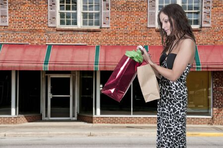 A beautiful young woman texting while on a shopping spree photo