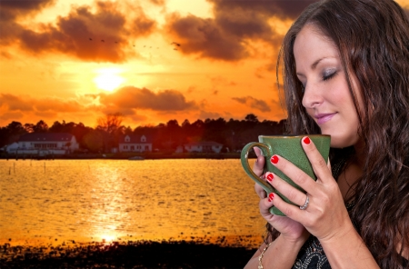 tea hot drink: A beautiful young woman drinking coffee at the beach in the morning Stock Photo