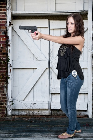 policewoman: Beautiful police detective woman on the job with a gun