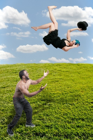 Handsome man catching a beautiful young woman falling through the sky Stock Photo - 13545356