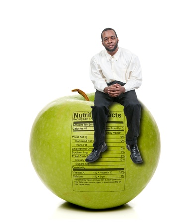 A handsome young man sitting on a green apple with a nutrition label photo