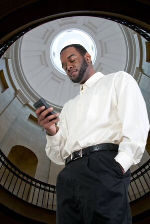 Black African American business man using a cell phone for texting photo