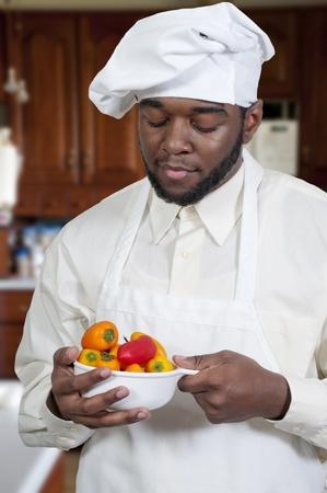 Black African American mannelijke chef-kok met een kom verse paprika's Stockfoto