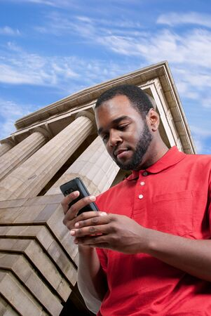 Black African American man using a cell phone for texting photo