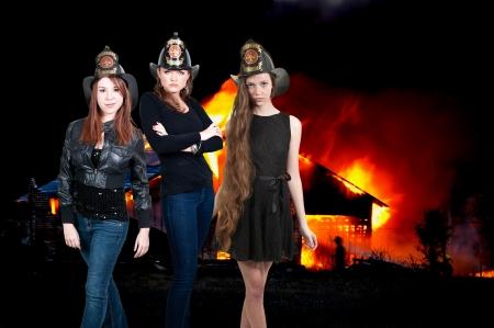 Beautiful women firefighters at a blazing fire photo