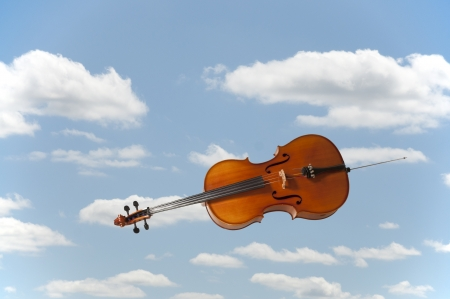 Beautiful wooden musical instrument known as the cello falling or flying through the sky photo