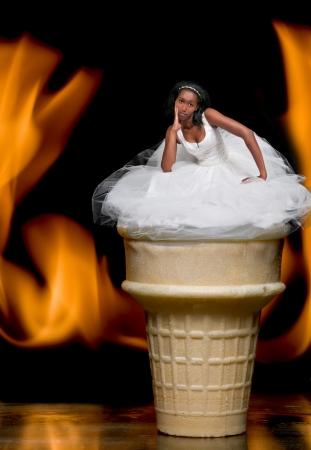 Schöne junge Braut in einem Hochzeitskleid auf einem lodernden Ice Cream in einem Wafer Kegel auf Feuer. Standard-Bild - 14878502