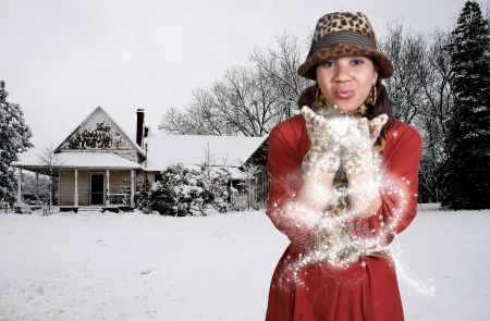 Beautiful black African American woman blowing snow off of her hands Stock Photo - 14880038