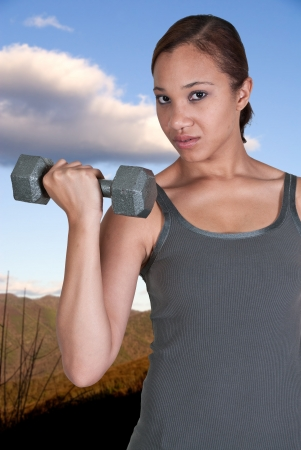 Beautiful young black African American woman using weights during a workout photo
