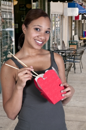 asian afro: A beautiful black African American woman eating Chinese Japanese or Asian takeout food Stock Photo