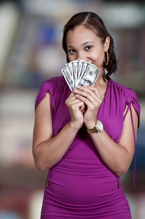 Beautiful woman holding a hand full of 100 dollar bills photo