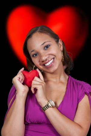 A beautiful young African American black woman holding a Valentines Day heart photo