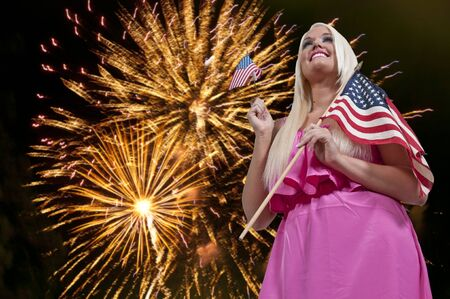 Beautiful woman holding a US flag at a firworks display Stock Photo - 14878878
