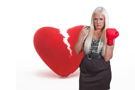 A beautiful woman in wearing a boxing glove in front of a broken heart - heartbreaker Stock Photo - 14880214