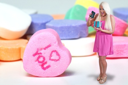 A beautiful young woman holding a Valentines Day heart and candy photo