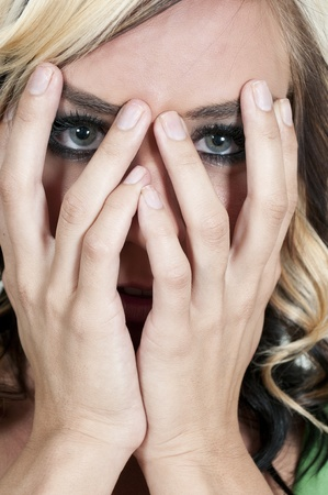 Beautiful young scared or surprized woman looking through her hands photo