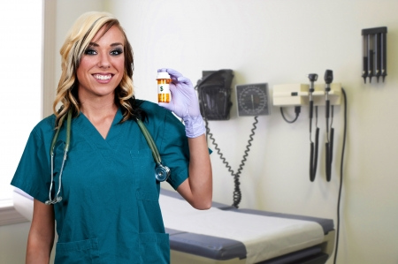A beautiful young female doctor on her rounds holding a prescription bottle of medicine pills Imagens - 14880288