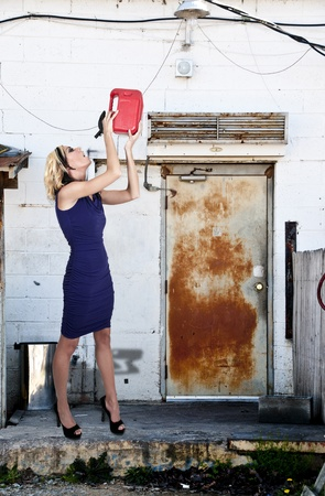 petrol can: Beautiful woman drinking from a gasoline petrol can container Stock Photo