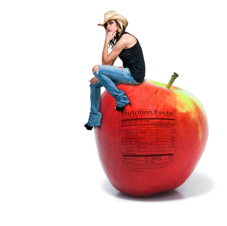 Beautiful young woman sitting on a whole red delicious apple with a nutrition label photo