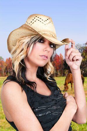 Beautiful young country girl woman wearing a stylish cowboy hat photo
