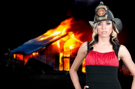 Beautiful young woman firefighter at a fire photo