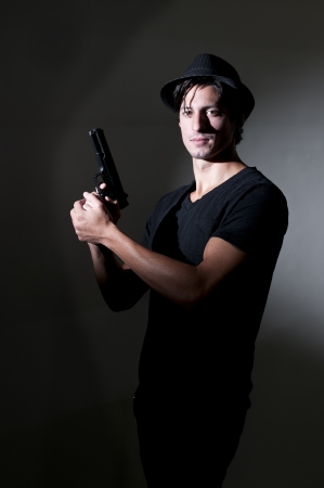 private i: Handsome police private detective man on the job with a gun