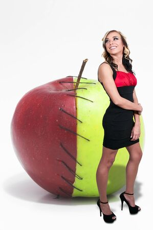 Beautiful woman standing beside a whole red and green apple photo