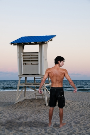Male lifeguard standing on the beach by a lifeguard stand photo