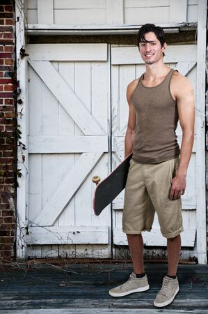 Handsome young man with a skateboard ready to ride photo