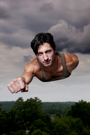 Handsome man super hero flying through the sky Stock Photo
