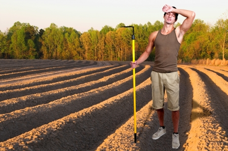 Man farmer with a hoe in the furrows of a freshly plowed field
