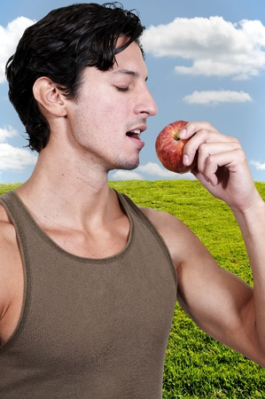 Handsome young man eating a fresh delicious apple photo