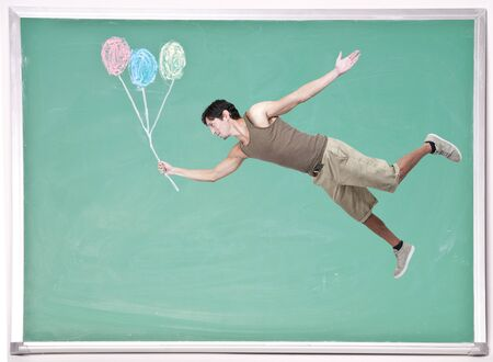 Handsome young man floating with balloons on a chalkboard photo