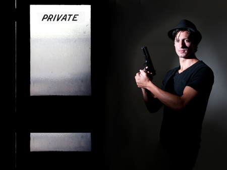 private security: Handsome police private detective man on the job with a gun