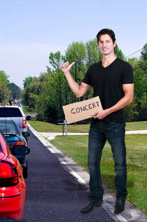 hitch hiker: Handsome man with a sign hitch hiking to a concert Stock Photo