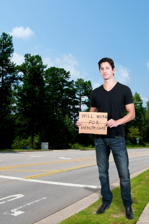 Handsome man holding a sign that says will work for healthcare photo