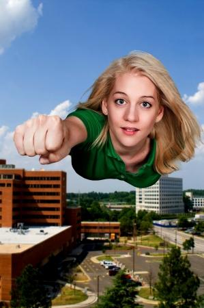 donna volante: Bella donna super eroe vola attraverso il cielo
